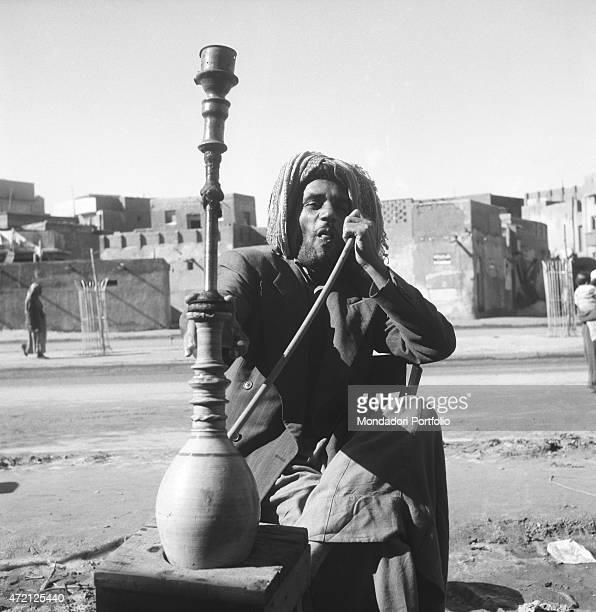 'Kuwaiti man smoking narghile sitting in the street Kuwait City December 1956 '