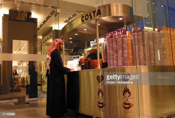 A Kuwaiti man stops at a COSTA Coffee stand January 23 2003 at Villa Moda one of the upscale shopping malls in Kuwait City Kuwait Villa Moda is owned...