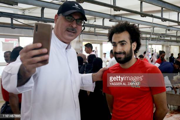 A Kuwaiti man takes a selfie picture with Egyptian butcher Mohammad Ibraheem aged 27 at a slaughterhouse in Kuwait City on August 13 during the third...