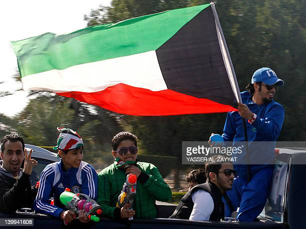 A Kuwaiti man waves his national flag as people drive through a street during celebrations marking the Gulf state's 51st Independence Day and the...