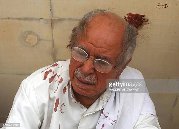 A Kuwaiti man with bloodstained clothes reacts as he sits at the site of a suicide bombing that targeted the Shiite AlImam alSadeq mosque during...