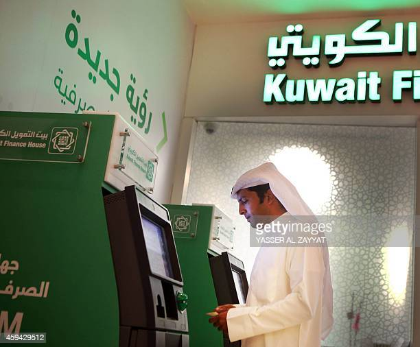 Kuwaiti man withdraws cash from an ATM outside a Kuwait Finance House branch inside the Avenues Mall the largest shopping centre in Kuwait on...