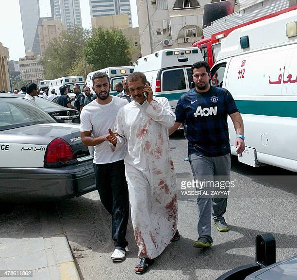 Kuwaiti men accompany a man with bloodstained clothes at the site of a suicide bombing that targeted the Shiite AlImam alSadeq mosque after it was...