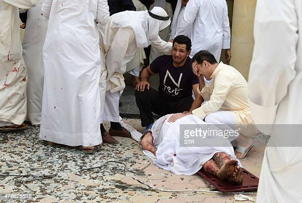 Kuwaiti men react over a body at the site of a suicide bombing that targeted the Shiite AlImam alSadeq mosque after it was targeted by a suicide...
