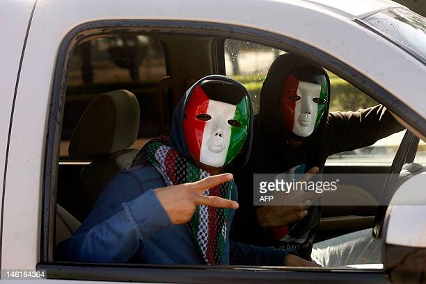 Kuwaiti men wearing masks in the colours of their national flag drive through a street in Kuwait City during celebrations marking the Gulf state's...