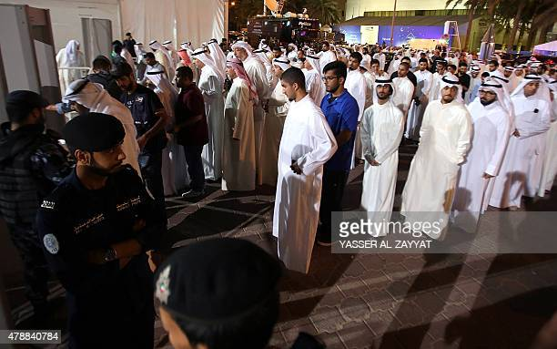 Kuwaiti mourners queue to be searched by security members outside the Sunni Grand Mosque on June 27 2015 as they arrive to give their condolences to...