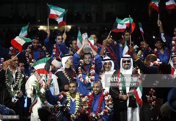Kuwaiti national football team goalkeeper and captain Nawaf alKhaldi holds the GCC cup trophy during a celebration upon the team's return to Kuwait...