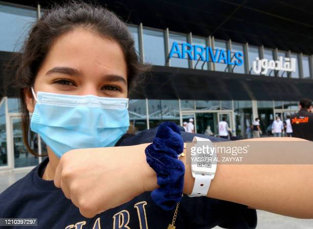 A Kuwaiti national residing abroad shows the tracking bracelet provided by authorities as she leaves at the Kuwait International airport in the...