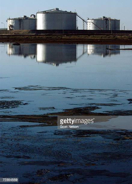 Kuwaiti oil production tanks are reflected in a lake of spilled oil at the Burgan oil field January 13 2003 in Central Kuwait The oil field the...