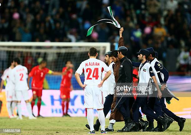 Kuwaiti police arrest a Syrian national and opponent of Syria's President Bashar alAssad after he ran onto the pitch waving an old national flag...