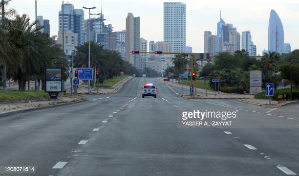 Kuwaiti police car patrols deserted streets in Kuwait city on March 23 a day after authorities declared a nationwide curfew amid the COVID19...