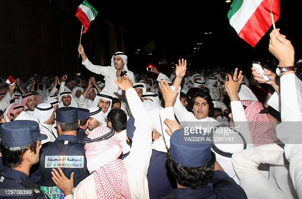 Kuwaiti police stop protesters, waving national flags, from approaching the parliament building in Kuwait City during a demonstration late on October...