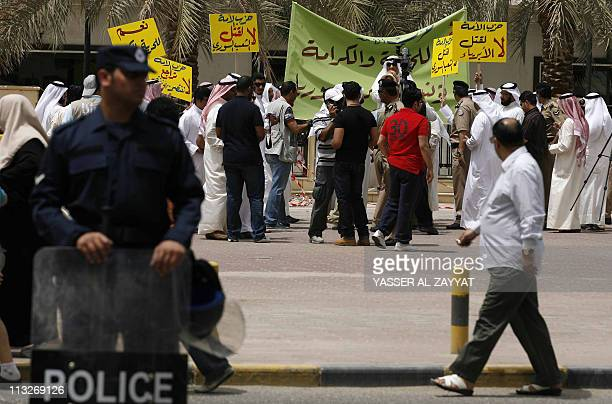 A Kuwaiti policeman stands guard as a group of men gather outside the Grand Mosque in Kuwait City to protest against the Syrian government's violent...