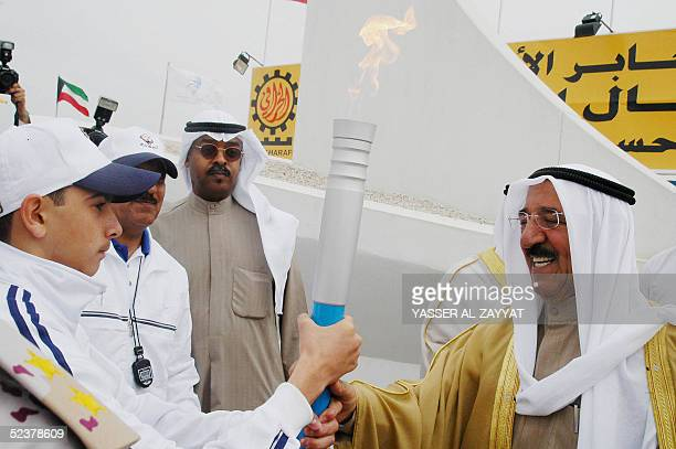 Kuwaiti Prime Minister Sheikh Sabah alAhmad alSabah holds a torch declaring the inauguration of the international Jaber alAhmad alSabah stadium in...