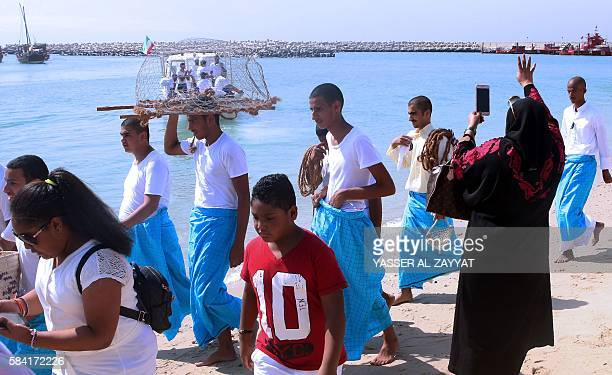 Kuwaiti sailors carrying traditional fishing nets on their head prepare to board Dhows ahead of a pearl diving trip on July 28 in Kuwait City...