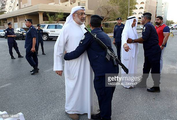 Kuwaiti security forces check Shiite Muslim men as they arrive to perform the morning prayer of the Eid al-Adha holiday at the al-Sadeq mosque in...