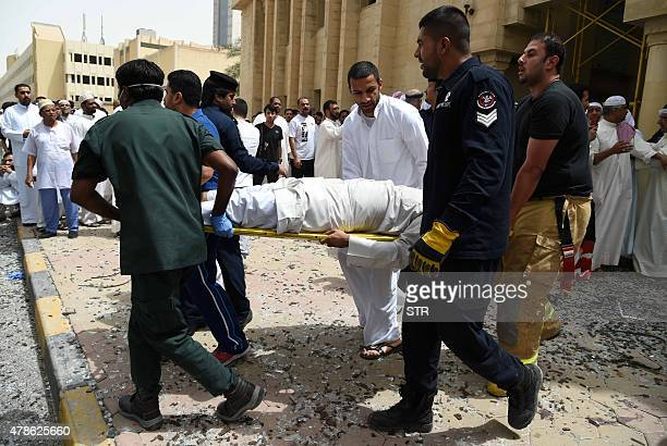 Kuwaiti security personnel and medical staff carry a man on a stretcher at the site of a suicide bombing that targeted the Shiite AlImam alSadeq...