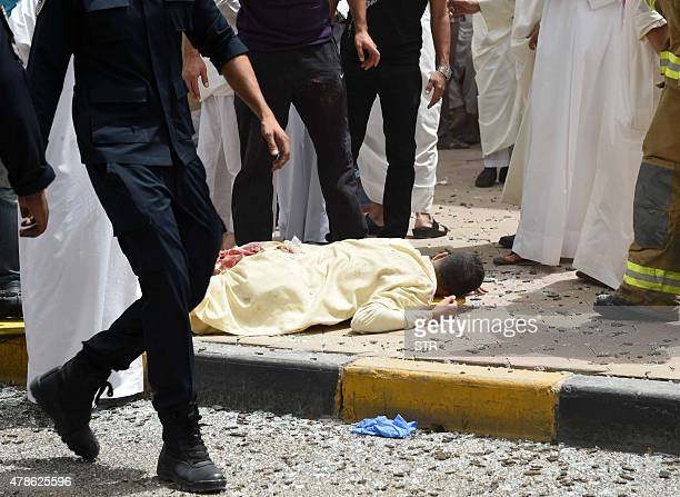 Kuwaiti security personnel walk past a body at the site of a suicide bombing that targeted the Shiite AlImam alSadeq mosque after it was targeted by...