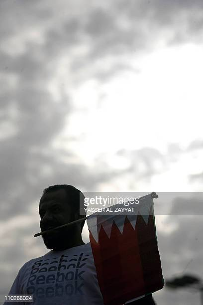 A Kuwaiti Shiite man holds a Bahraini flag with his teeth during a protest in support of Shiiteled Bahraini antigovernment protesters in Kuwait City...