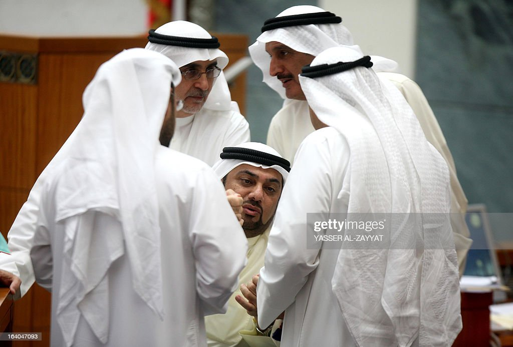 Kuwaiti Shiite member of parliament (MP) Yousef al-Zalzalah (C) speaks with fellow MPs as they attend a parliament session at the Kuwait national assembly in Kuwait City on March 19, 2013. Kuwait's parliament passed in principle a bill that requires the government to buy billions of dollars of bank loans owed by citizens and reschedule them after waiving interest.