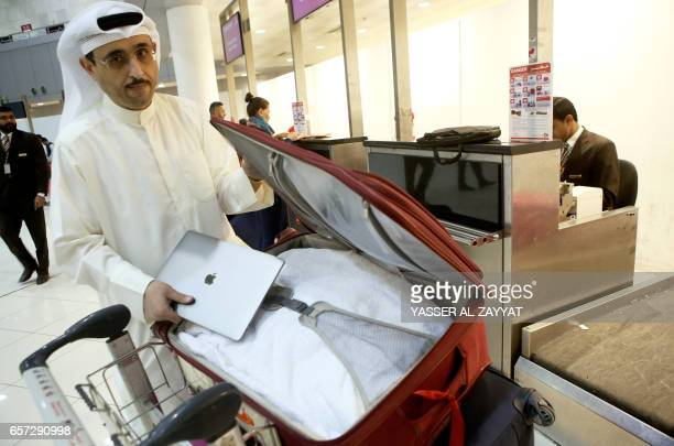 Kuwaiti social media activist Thamer alDakheel Bourashed puts his laptop inside his suitcase at Kuwait International Airport in Kuwait City before...