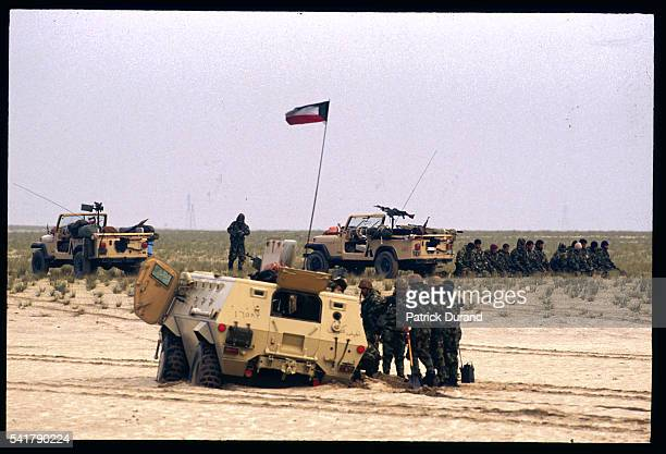 Kuwaiti soldiers gather round a damaged armored vehicle as Iraqi soldiers that surrendered wait in the background