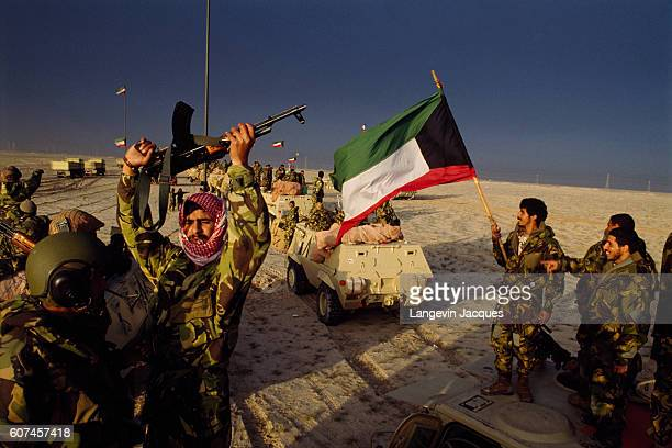 Kuwaiti soldiers proudly celebrating the taking back of their invaded country waving guns and their national flag The invasion of Kuwait by Iraqi...
