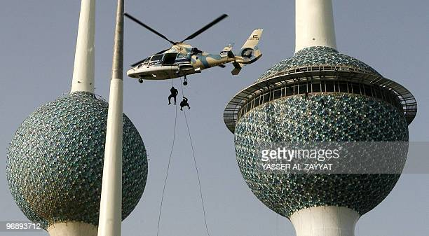 Kuwaiti special forces climb down a helicopter near the Kuwait Towers as they show their skills during celebrations marking the emirate's national...