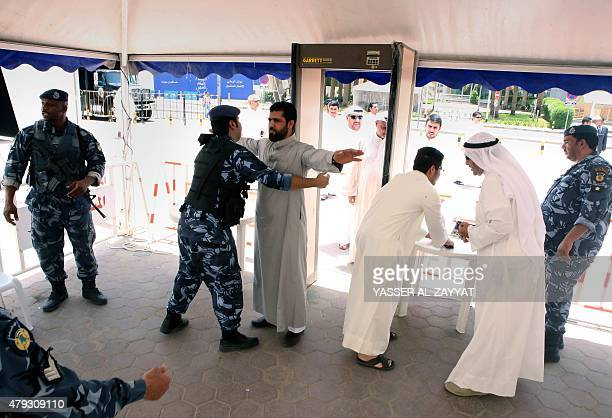 Kuwaiti Sunni and Shiite men are searched by security members outside the Sunni Grand Mosque as they arrive to perform Friday prayers together in an...