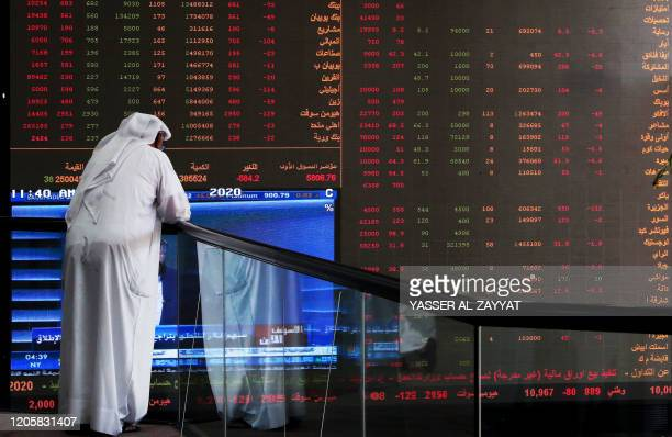 Kuwaiti trader checks stock prices at Boursa Kuwait in Kuwait City, on March 8, 2020. - Kuwait Boursa authorities stopped trading after the Premier...