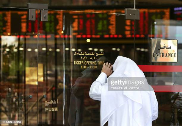 A Kuwaiti trader checks stock prices from the outside after authorities stopped trading at Boursa Kuwait in Kuwait City on March 8 2020 Kuwait Boursa...