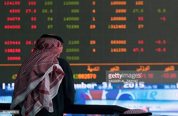 A Kuwaiti trader follows the stock market activity at the Kuwait Stock Exchange on December 31 2015 in Kuwait City Stock markets in the energyrich...