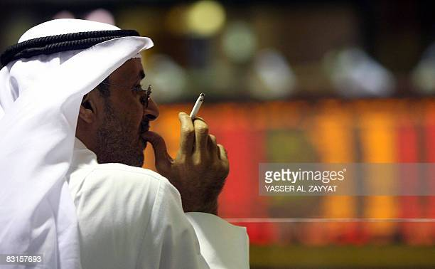 A Kuwaiti trader smokes a cigarette as he follows the market's movement at the Stock Exchange in Kuwait City on October 7 2008 The Kuwait Stock...