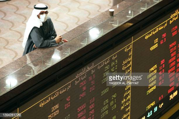 Kuwaiti trader wearing a protective mask follows the market at the Boursa Kuwait stock exchange in Kuwait City on March 1, 2020. - Boursa Kuwait...