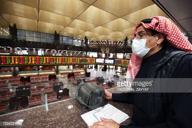 A Kuwaiti trader wearing a protective mask follows the market at the Boursa Kuwait stock exchange in Kuwait City on March 1 2020 Boursa Kuwait...