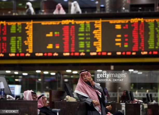Kuwaiti traders follow stock prices at Boursa Kuwait stock market, in Kuwait City on January 6, 2020. - Gulf stock markets were hit by a panicky...