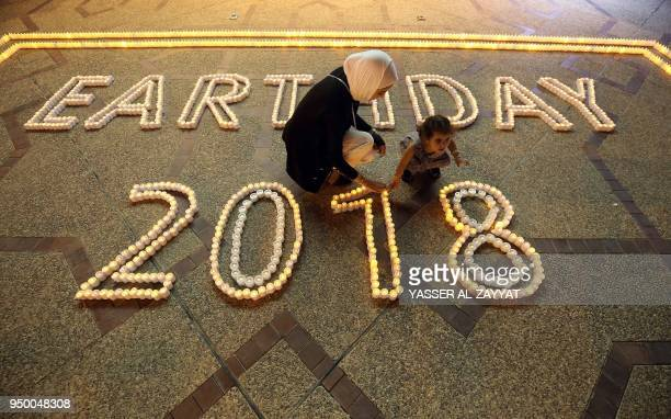 A Kuwaiti woman and child light candles as they mark International Earth Day in Kuwait City on April 22 2018