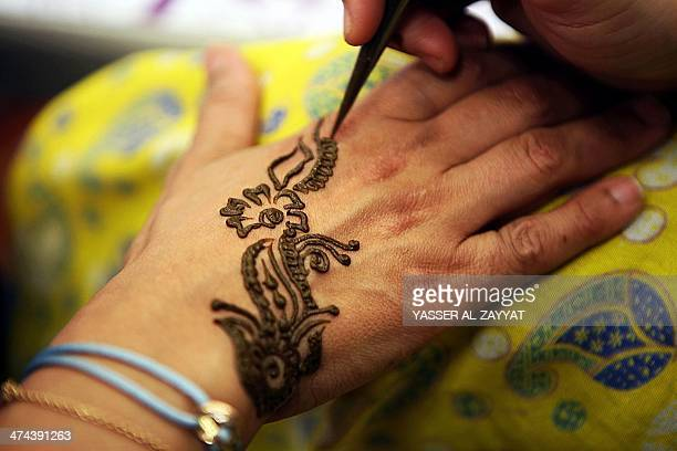 A Kuwaiti woman gets her hand decorated with traditional henna at a market in downtown Kuwait City on February 23 2014 Kuwaiti women traditionally...