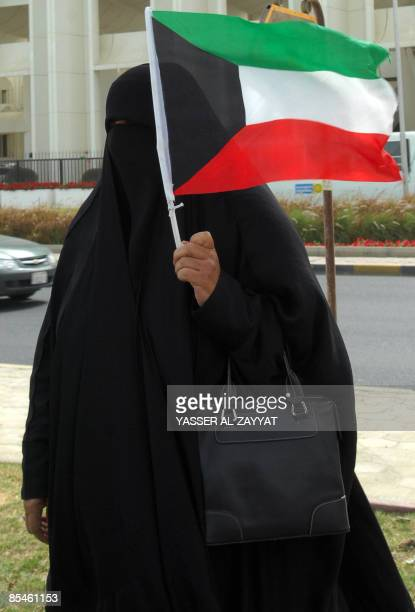 Kuwaiti woman hold her national flag during a protest outside the national assembly in Kuwait City on March 17, 2009 demanding from the Emir of...