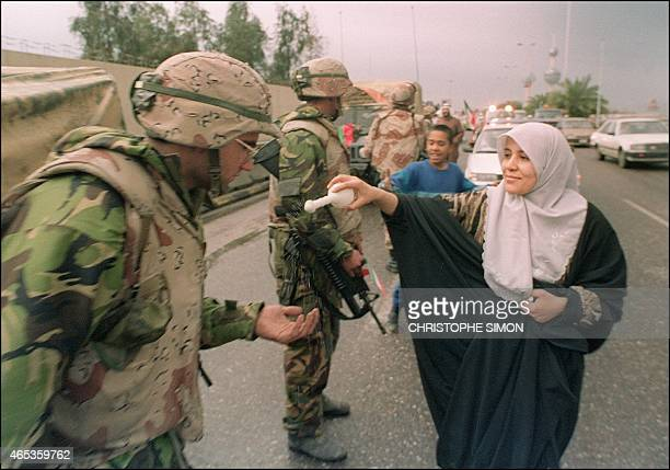 A Kuwaiti woman offers rosewater to a US soldier as a sign of welcome 27 February 1991 after allied forces rolled into Kuwait City 27 February 1991