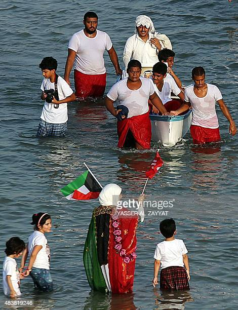 A Kuwaiti woman waves her national flag as she welcomes pearl divers upon their arrival at the main beach in Kuwait City at the end of the 27th...