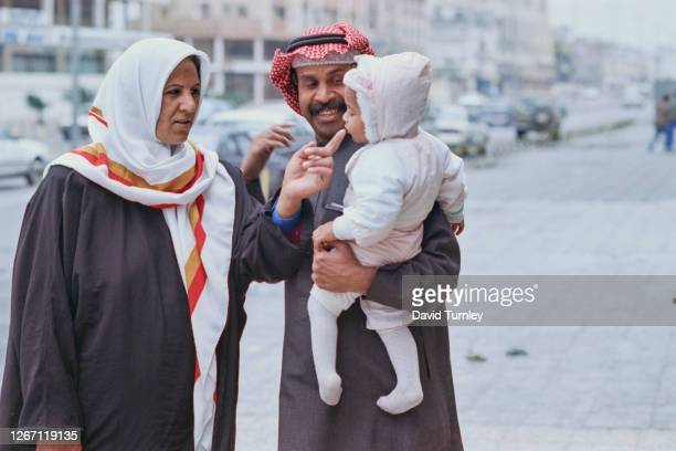 Kuwaiti woman wearing a hijab has her finger kissed by a young child held in the arms of a Kuwaiti man wearing a keffiyeh after the liberation of...
