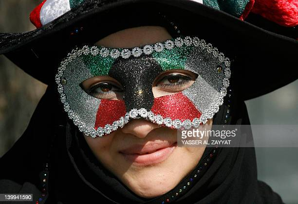 A Kuwaiti woman wearing a mask in the colours of her national flag attends celebrations marking the Gulf state's 51st Independence Day and the 21st...