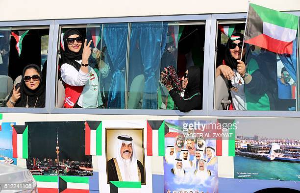 Kuwaiti women flash the sign for victory and wave their national flag during celebrations marking the Gulf state's 55th Independence Day and the 25th...