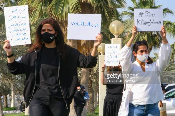Kuwaiti women raise placards during a rally to denounce violence against women, outside the National Assembly, in the capital Kuwait City, on April...
