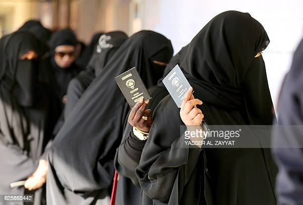 TOPSHOT Kuwaiti women show their passports as they arrive at a polling station to cast their votes for the parliamentary elections in Kuwait City on...