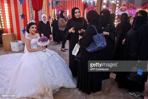 Kuwaiti women watch as a model displays a wedding dress and make up during a beauty exhibition for Kuwaiti beauty expert Hanan Dashti on October 25...