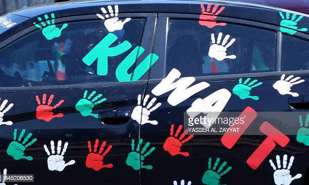 Kuwaitis drive a car bearing stickers in the colours of the national flag during celebrations marking the country's 56th Independence Day and the...
