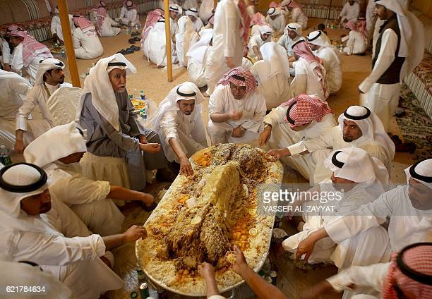 Kuwaitis eat a traditional Kuwaiti feast made from camel meat during an election campaign meeting for Kuwaiti candidate AlHumaidi alSubaei for the...