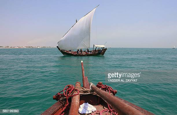 Kuwaitis sail on traditional dhows during the annual pearl diving season on August 2 2016 off the coast of the port city of Khairan 100 kilometres...